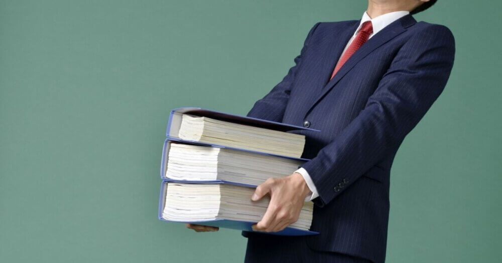 複数冊の本を持つ男性