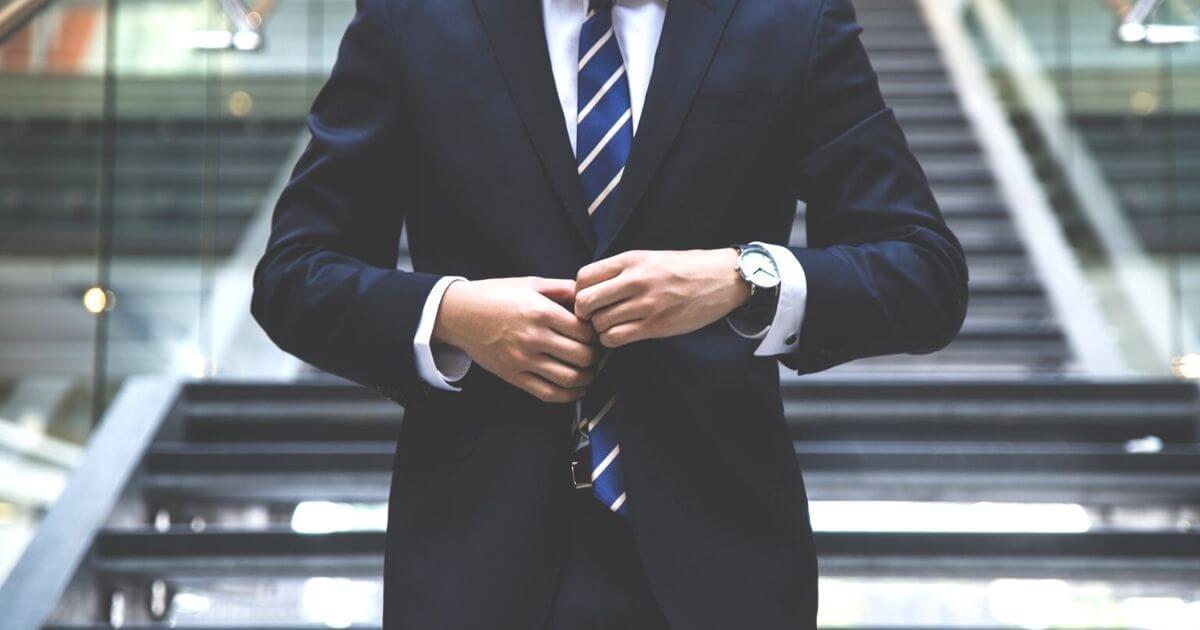 スーツのボタンを留める男性